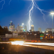 lightning above kansas city skyline with highway traffic motion