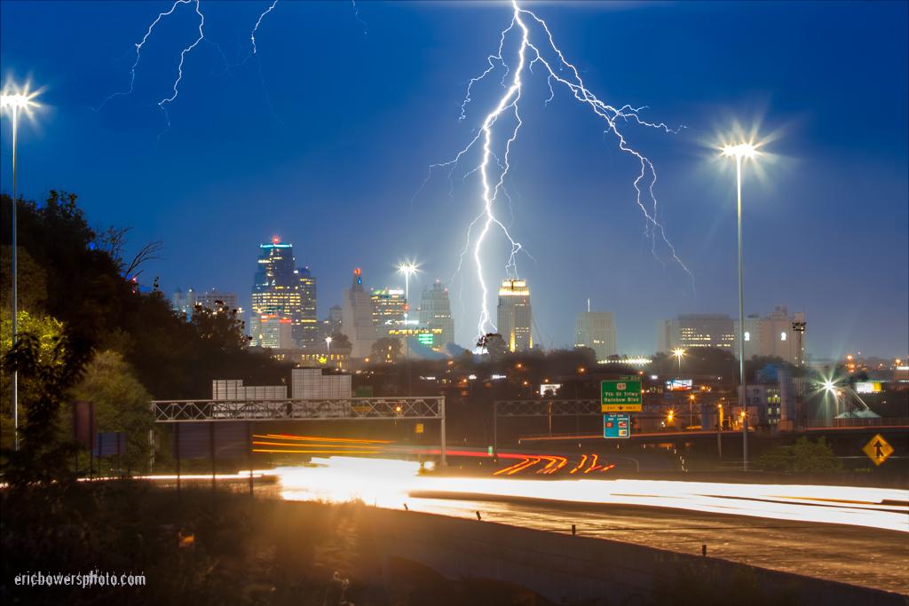 lightning above kansas city skyline with highway traffic motion